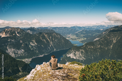 Young man relaxing on the edge of mountain and enjoying wonderful view Poster