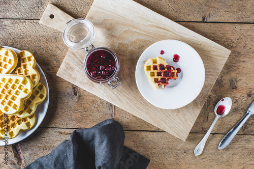 Homemade wafers and raspberry jam on a wooden table. Top view and flat lay