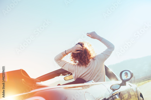 Young woman resting in a convertible at sunset enjoying the view