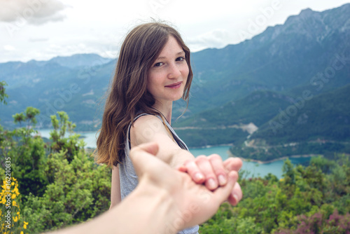 Follow me, Attractive brunette girl holding hands with leads in mountain valley Poster