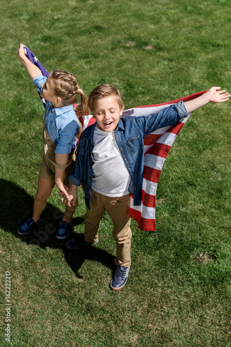 happy siblings with american flag having fun outdoors, celebrating 4th july - Independence Day
