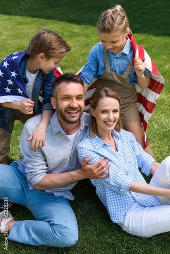 Happy family with american flag hugging outdoors, Independence Day concept