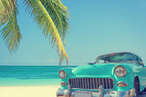 Classic car on a tropical beach with palm tree, vintage process - 162225694