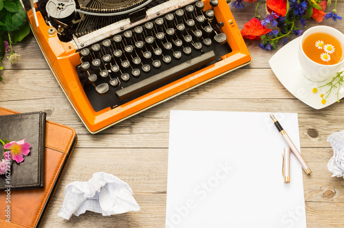 Workspace with orange vintage typewriter with white blank. Bouquet of summer field flowers, pen and cup of chamomile tea.