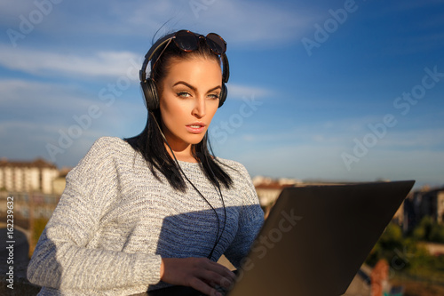 Woman online shopping by laptop outdoor