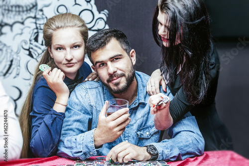 Friends beautiful young successful gambling in casino you play poker at a table плакат