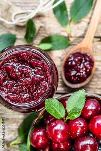 Homemade jam from cherry in jar and cherries in a bowl, overhead © alicja neumiler