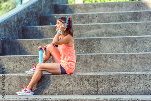 Sporty jogging girl sitting outdoors resting after  training listening music