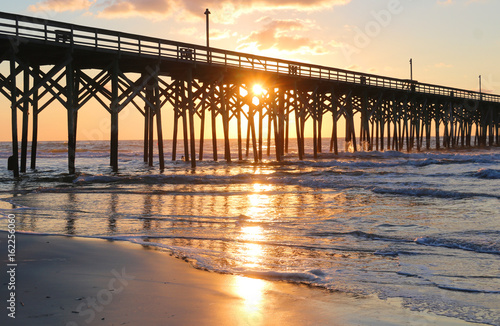 Sunrise at a South Carolina Atlantic coast, Myrtle Beach area, USA. Landscape with the reflection of the sun in shallow water on the foreground and a wooden pier on the background.Vacation background.