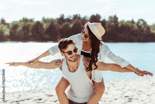 Handsome young man in sunglasses piggybacking smiling girl in straw hat at beach
