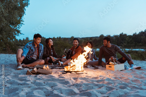 young multiethnic friends resting near campfire on sandy beach