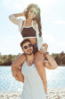 happy couple piggybacking while spending time on beach on summer day
