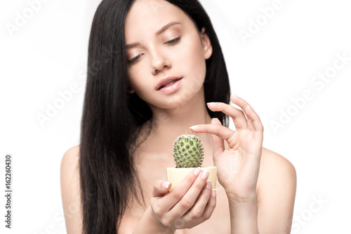 Beautiful young brunette woman holding cactus in pot and touching thorns