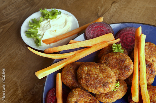 Fish cutlets with carrots, beetroots and mayonnaise sauce.  Homemade fried  cutlets in plate on wooden table. - 162275048