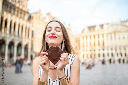 fototapeta na ścianę Young and happy woman with dark chocolate bar standing outdoors on the Grand place in Brussels in Belgium. Belgium is famous of its chocolate