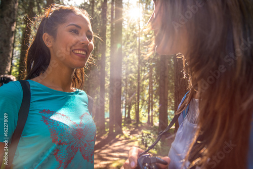 Woman smiling to friend at hiking trail path in forest woods during sunny day Poster