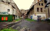 Opustoszałe Łódzkie podwórze, ze zrujnowanymi blokami i zniszczonymi witrynami