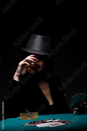 Studio shot of beautiful young woman playing poker. плакат