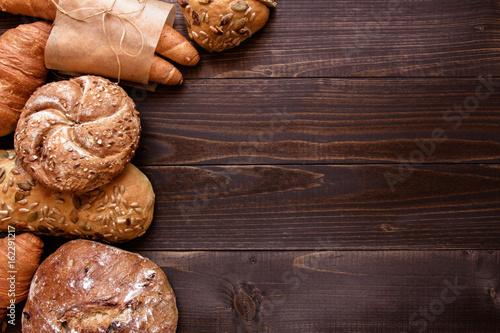 Fototapeta Fresh bread on the dark wooden background top view