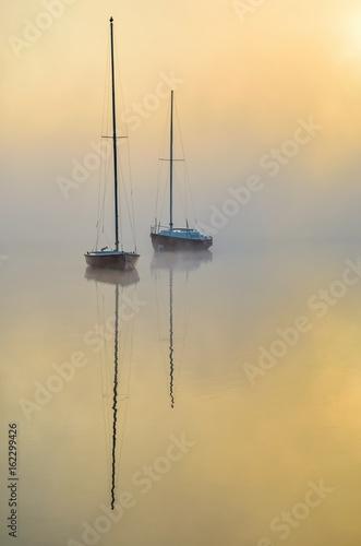 Poster Minimalist foggy morning landscape. Boats on the lake.