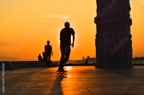 Young man skateboarder skateboarding at sunset, silhouette.