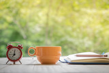 cup of coffee with notebook, pen and alarm clock on a Desktop from wooden plank in natural background. - 162306290