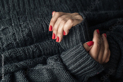 A woman in a dark knitted sweater shows a red manicure close-up.