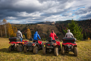 Rear view of four men at quad bikes prepared to go down the hill. Beautiful landscape of rolling countryside and colorful forest under the sky with cumulus clouds in autumn
