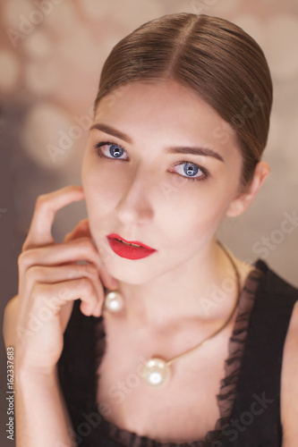 Close up indoor, studio portrait of young attractive woman with beautiful classic makeup, red lips posing on background. Female beauty, fashion concept © olgakok