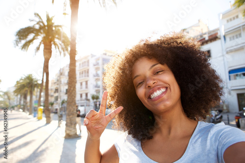 happy woman making peace sign outside