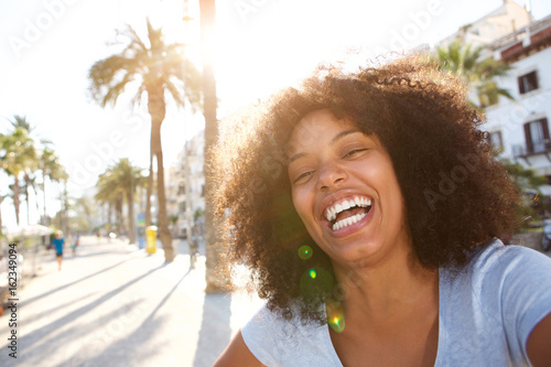 Selfie portrait of laughing woman with curly hair