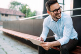 Portrait of businessman in glasses holding tablet - 162350222