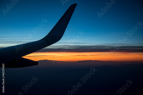 View of airplane wing flying at sunset Poster