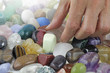 Close up of Crystal healer choosing a tumbled healing stone - female hand picking a lime colored stone from a random selection of tumbled stones fading to white providing copy space
