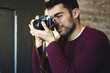 Cropped image of talented male photographer making creative photos on vintage camera indoors.Professional hipster guy dressed in casual outfit taking picture spending free time on favourite hobby