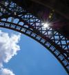 Sun shining through Eiffel Tower. Colorful beams and spots. Paris (France)