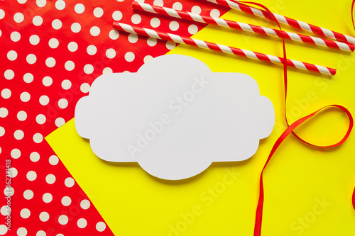 festive background with Red and White striped straws and wrapping paper and ribbon
