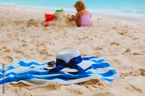 family at beach- towel, sunglasses and girl play with sand