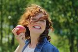 jolie femme rousse souriante mangeant pomme dans nature