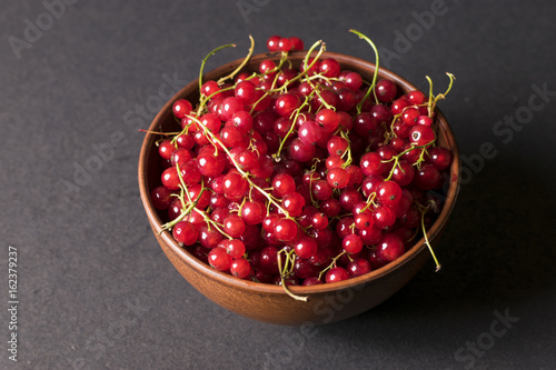 Fresh red currants in plate on dark wooden table.