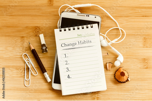 Hand written  Change habits message notepad with the  pencil  on wooden table for change habits  list for good life concept , overhead shot or Top view