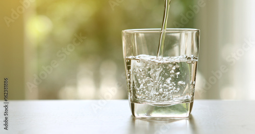 Zamyka w górę dolewanie oczyszczonej świeżej napój wody od butelki na stole w żywym pokoju