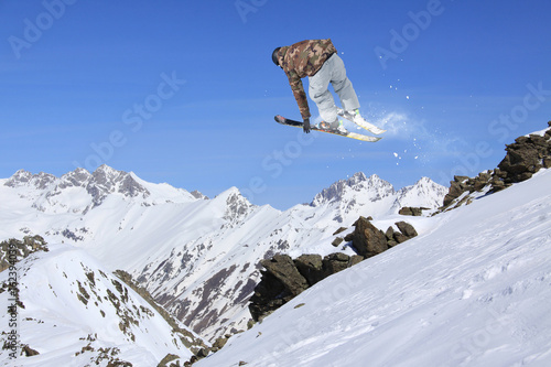 Flying skier in the mountains. Extreme freeride sport. Poster