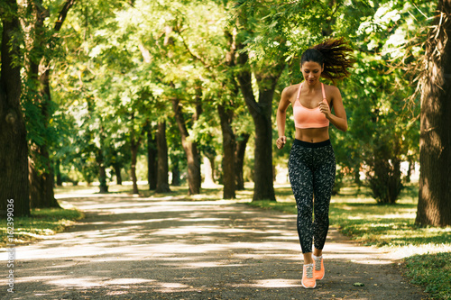 In de dag Jogging Athletic fit young woman jogging running outdoors early morning in park.