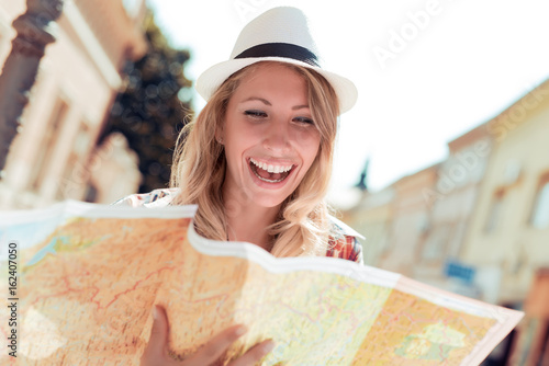 Happy young woman using a city map Poster