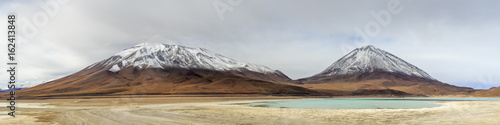 Two snowy mountains and a light blue lake Poster