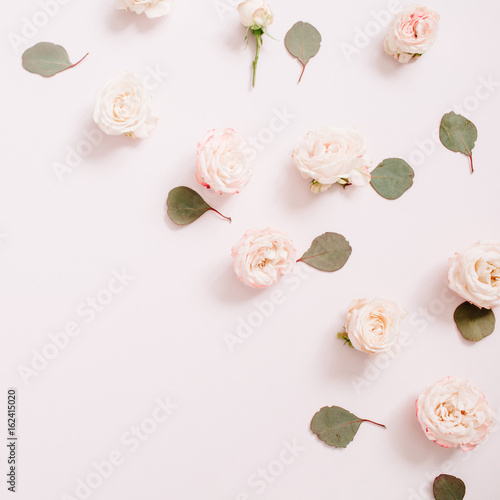 Flowers pattern made of beige roses, eucalyptus branches on pale pastel pink background. Flat lay, top view. Floral texture background. - 162415020