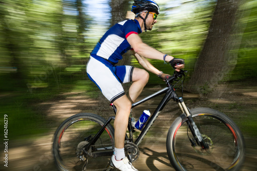 Handsome young man cycling in the mountain.