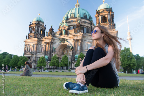 Pretty gil sitting in front of Berlin Cathedral wearing sunglusses © Roman Stetsyk