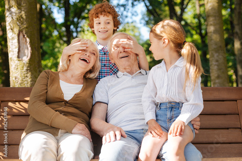 Happy grandparents spending time with children